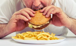 Close up of man eating hamburger